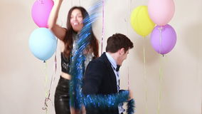 Slow motion of happy crazy couple enjoying dancing in photo booth. Happy crazy couple enjoying dancing in party photo booth, in slow motion stock video footage