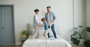 Slow motion of family mother father son jumping on bed in bedroom having fun stock video