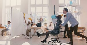 Slow motion happy female employee riding chair along modern office, fun business people celebrate achievements together. Young crazy excited team throw paper stock video footage
