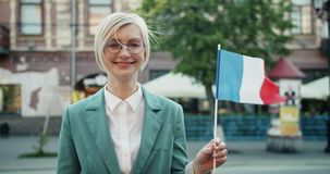 Slow motion of happy French girl holding national flag smiling standing outdoors. Alone looking at camera feeling proud for country. Tourism and youth concept stock footage