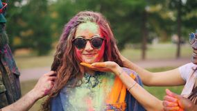 Slow motion of happy friends painting pretty girl`s face and hair with powder paint at Holi festival, woman is smiling. Slow motion of happy friends painting stock video
