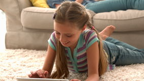 In slow motion happy girl using digital tablet on rug with mother reading book in background stock video