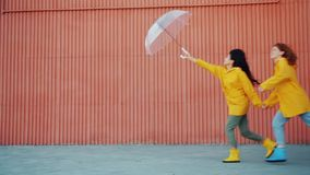 Slow motion of happy girls friends in raincoats running outdoors with umbrella. Holding hands enjoying autumn day. Lifestyle, friendship and weather concept stock video
