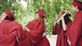 Slow motion of happy graduates wearing gowns and mortar-boards hugging, laughing and congratulating each other on
