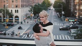 Slow motion happy Hispanic man holding European girl in arms. Young romantic couple spinning on a bridge in New York. Cheerful multiethnic boyfriend and stock video footage