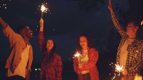 Slow motion of men and women dancing and jumping outdoors with burning sparklers, having fun, celebrating holiday and. Slow motion of happy men and women dancing stock video