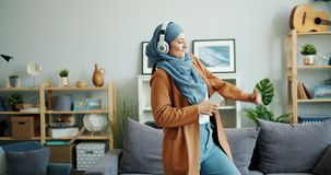 Slow motion of happy mixed race girl in hijab dancing in headphones at home. Holding smartphone having fun alone in apartment. Modern lifestyle and people stock video