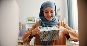 Slow motion of happy mixed race lady in hijab opening box taking present smiling. Enjoying present. Modern people, lifestyle and holidays concept stock video footage