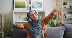Slow motion of Muslim girl in hijab enjoying music in headphones dancing at home. Slow motion of happy Muslim girl in hijab enjoying music in headphones dancing stock video