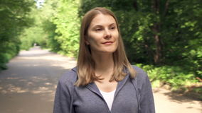 Slow Motion Happy smiling young woman in hoodies walking around in sunny park on summer`s day. Green trees foliage around stock video footage