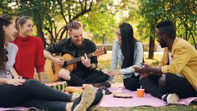 Slow motion of happy students playing the guitar and enjoying music in park on picnic in autumn, guitarist is playing