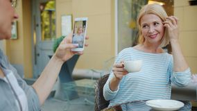 Slow motion of happy woman taking photo of pretty blonde in outdoor cafe. Slow motion of happy woman taking photo of pretty blonde holding cup of tea in outdoor stock video