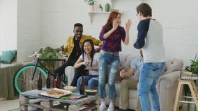 Slow motion of happy young friends watching sports game on TV jumping and celebrating victory of favourite team at home. Indoors stock footage