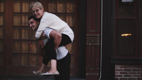 Slow motion happy young Hispanic man carrying his girlfriend on his back laughing, enjoying romantic fun date outside. Young romantic couple sharing cheerful stock video