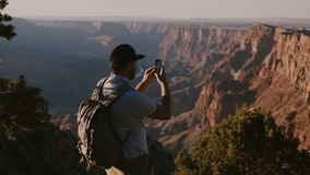 Slow motion happy young tourist man with backpack taking smartphone photo of epic summer sunset over Grand Canyon USA. Male traveler hiking, living healthy stock video