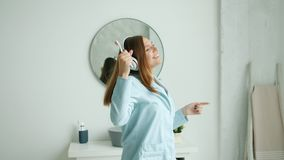 Slow motion of happy woman in headphones brushing teeth dancing in bathroom. Slow motion of happy young woman in wireless headphones brushing teeth dancing stock video