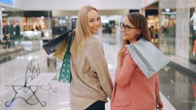 Slow motion of happy young women friends walking together in shopping mall holding bright bags then turning to camera