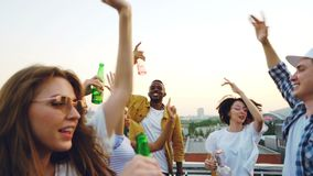 Slow motion of happy youth dancing at outdoor party on roof having fun and relaxing at weekend holding bottles. Modern