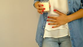 Slow motion. Healthcare and medical concept.. Woman hand holding glass of milk having bad stomach ache because of