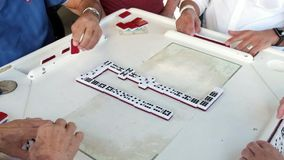 Playing domino game video. Slow motion high definition video of elderly individuals playing the popular domino game stock footage