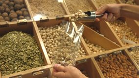 Peeled nuts and seeds.  A man`s hand puts pistachios in a bag. Slow motion. Horizontal pan  from left to right stock video