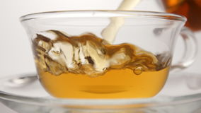 SLOW MOTION: Hot tea flowing to a tea cup - close up stock video footage