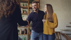 Slow motion of housing agent giving keys to buyers of new apartment, happy husband and wife are hugging and kissing, man