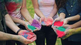 Slow motion of human hands holding multicolor powder paint gulal for Holi festival ceremony standing outside on lawn. Slow motion of human hands holding stock video