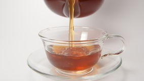 SLOW MOTION: Human pours a tea in a cup from a teapot - close up stock footage