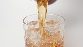 SLOW MOTION: Human pours a whiskey in a glass with an ice cubes from a bottle - close up stock footage