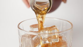 SLOW MOTION: Human pours a whiskey in a glass with an ice cubes - close up stock footage