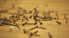 Slow motion of hundreds of screws falling on wooden table, slide right, close up