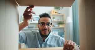 Slow motion of joyful African American man opening box looking inside smiling stock video footage