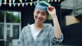 Slow motion of joyful Asian hipster raising sunglasses smiling outdoors. Slow motion of joyful Asian hipster with blue dyed hair and nose piercing raising stock video