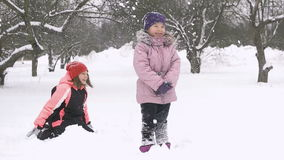 Slow motion of joyful kids playing in snow. Two happy girls having fun outside winter day stock video