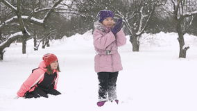 Slow motion of joyful kids playing in snow. Two happy girls having fun outside winter day.  stock video footage