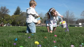 Slow motion of kids having fun gathering eggs at Easter hunt. Slow motion of kids in nice clothes having fun, running at the field on green grass, gathering