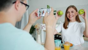 Slow motion of lady posing with apples when guy taking photo with smartphone. Slow motion of young lady posing with apples having fun when guy is taking photo stock footage