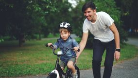 Slow motion of laughing child cycling in park with careful father who is teaching him to ride bicycle. Happy young