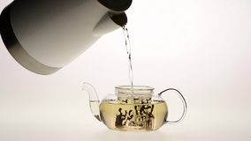 Slow motion, leaves of green tea are brewed in teapot stock video footage