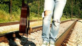 Slow-motion lengte van een kerel die langs de spoorweg in scheuren-omhooggaande jeans lopen stock footage