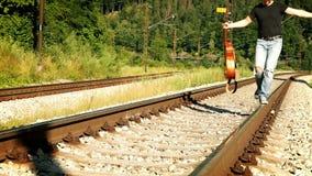 Slow-motion lengte van een tiener die langs de spoorweg met gitaar in zijn hand lopen stock videobeelden