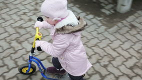 Slow motion. Little girl in a warm hat and jacket riding a mini scooter outdoors. stock footage