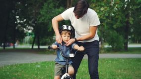 Slow motion of loving dad talking to his little son then putting protective bicycle helmet on his head while child is. Slow motion of loving dad talking to his stock footage