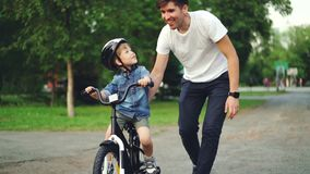 Slow motion of loving dad teaching his adorable son to ride bicycle in park holding bike and talking to child. Slow motion of loving dad teaching his adorable stock footage
