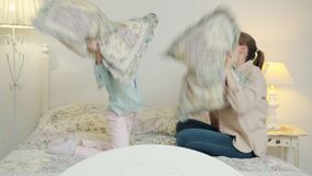 Slow motion of loving mother playing with joyful daughter fighting pillows then hugging