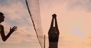 Young female volleyball players pass and spike the ball over the net on a sunny summer evening. Fit Caucasian girls. SLOW MOTION, LOW ANGLE, CLOSE UP, LENS FLARE stock video footage