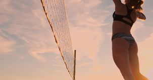 SLOW MOTION, LOW ANGLE, CLOSE UP, SUN FLARE: Athletic girl playing beach volleyball jumps in the air and strikes the