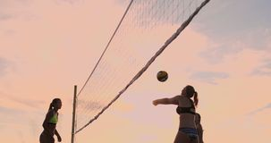 SLOW MOTION, LOW ANGLE, CLOSE UP, SUN FLARE: Athletic girl playing beach volleyball jumps in the air and strikes the. Ball over the net on a beautiful summer stock video footage