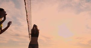 SLOW MOTION, LOW ANGLE, CLOSE UP, SUN FLARE: Athletic girl playing beach volleyball jumps in the air and strikes the. Ball over the net on a beautiful summer stock video
